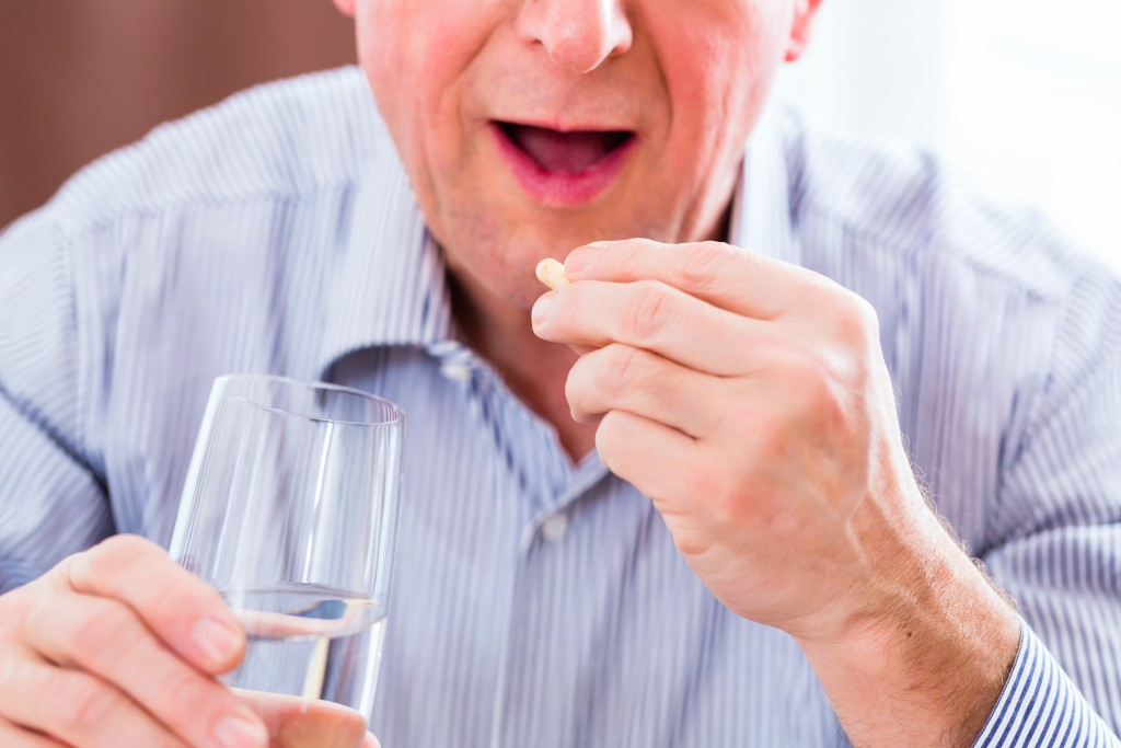 Old man taking overdoses medicaments at home