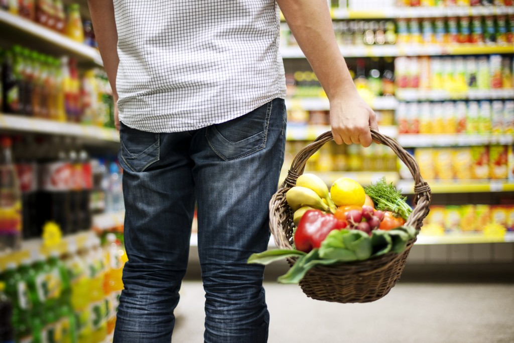 Man grocery shopping with fruits and vegetables in a basket