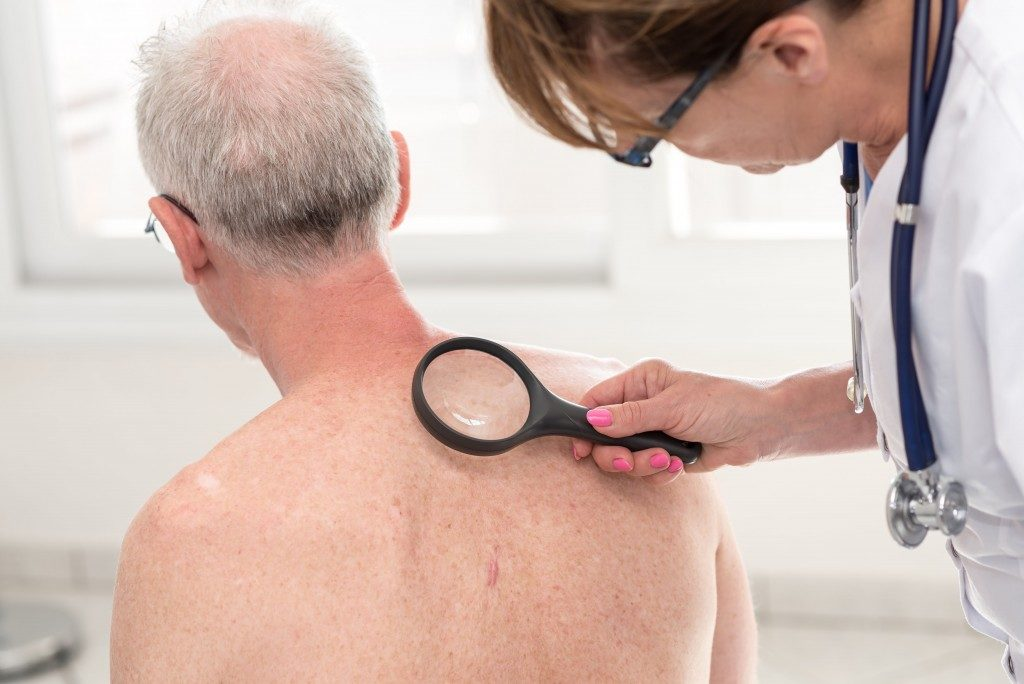 elderly man being examined for skin cancer