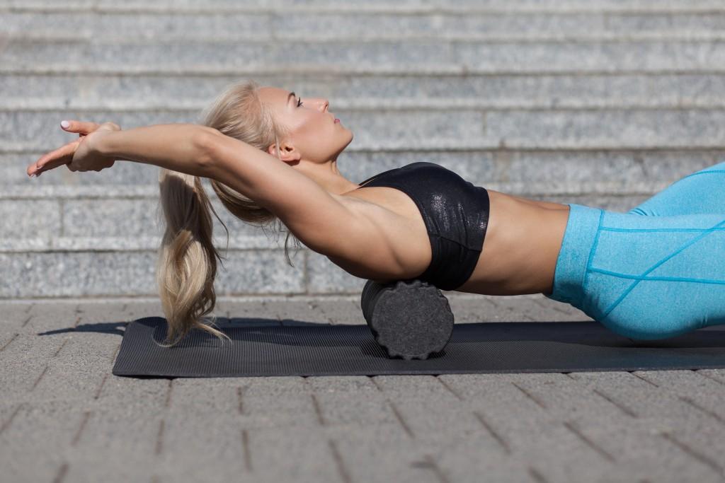 Woman rolling a foam roll on her back