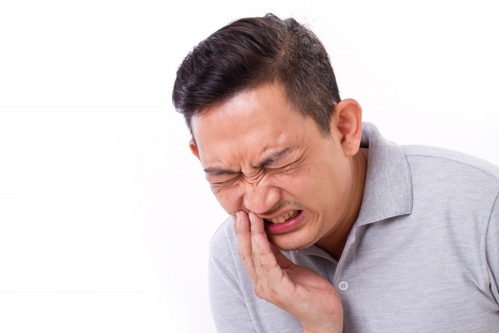 man with clecnhing jaw because of aching teeth