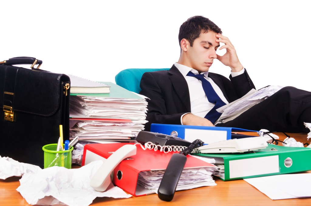 man having an headache with his cluttered desk