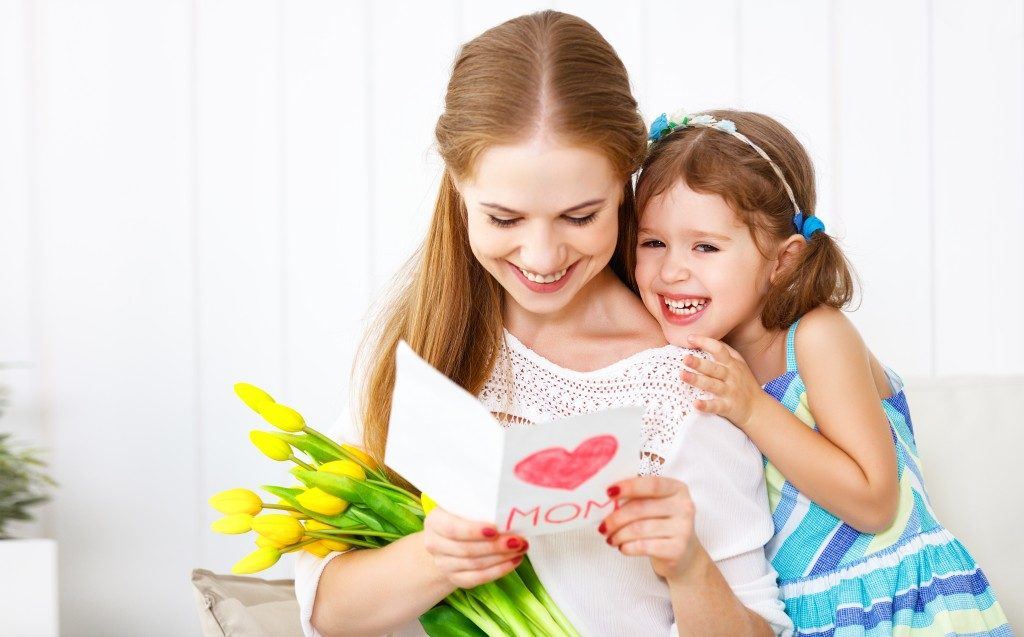 A littile girl showing her mom a card while she is holding flowers