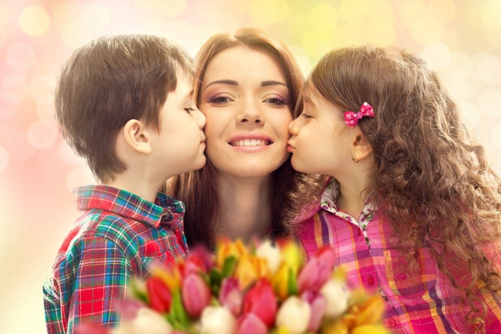 Portrait of children kissisng their mother with flowers
