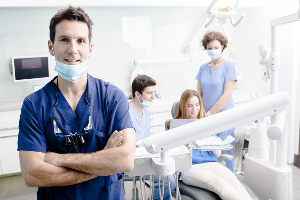 Denstist on his work place smiling with patient in the back