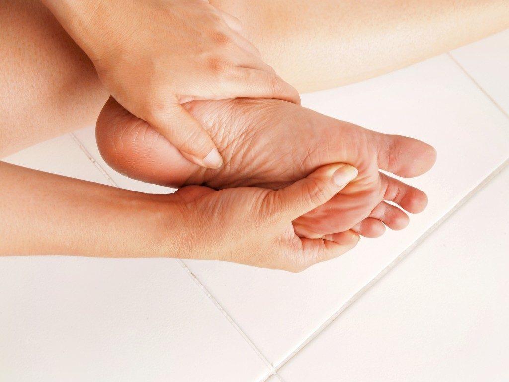 woman massaging her foot