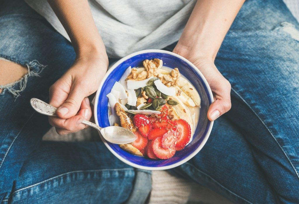person holding a small plate with fruits