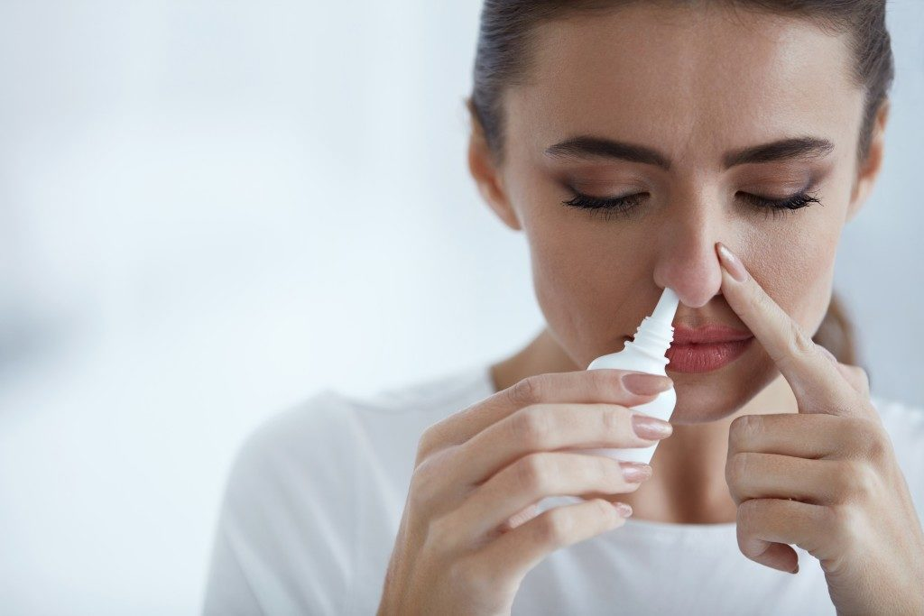 Woman putting solution in her nose